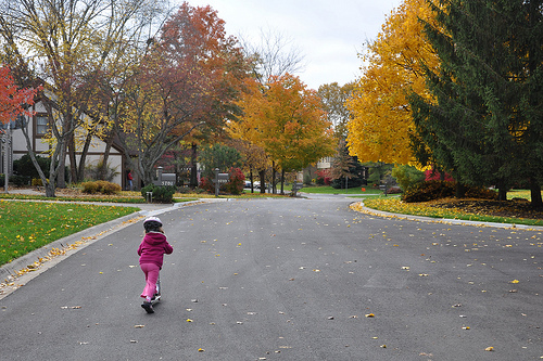 Alana scooters past the colors of autumn