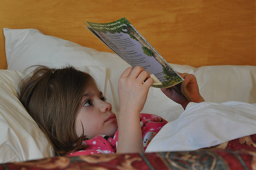 Alana reads in bed at the hotel